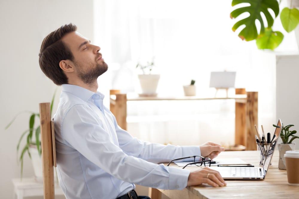 Entrepreneur détendu et heureux faisant face à son poste de travail.
