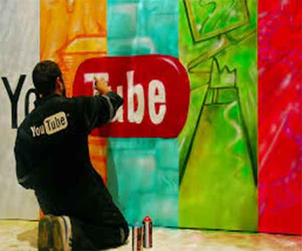 Artiste graphant le logo Youtube sur un décor de paysage